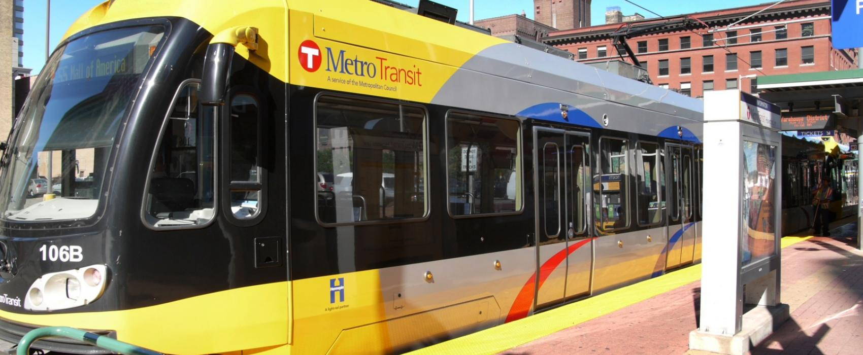A yellow Metro Transit light rail train at a station